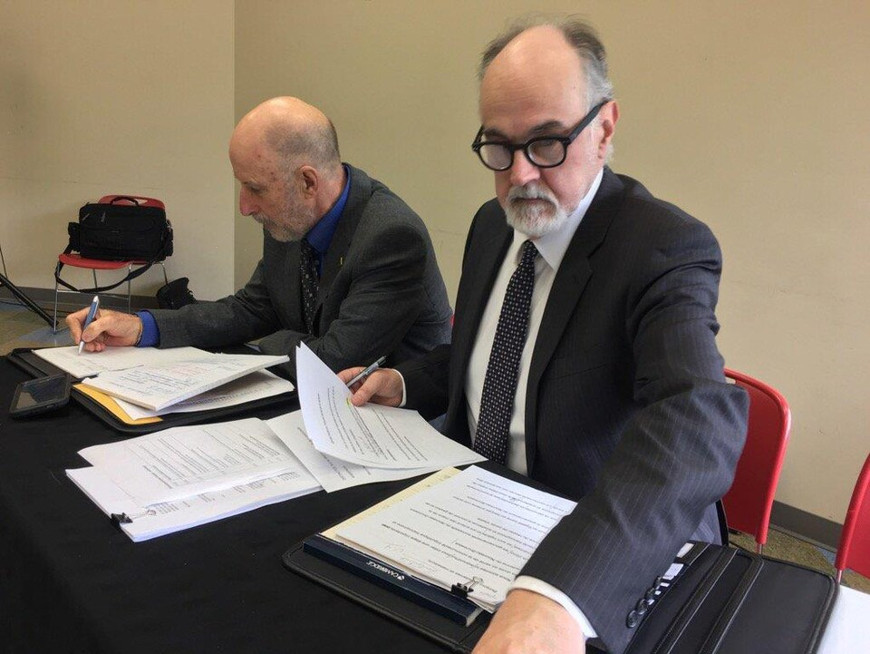 Jacques Verge et Hubert Dupuis assis à une table