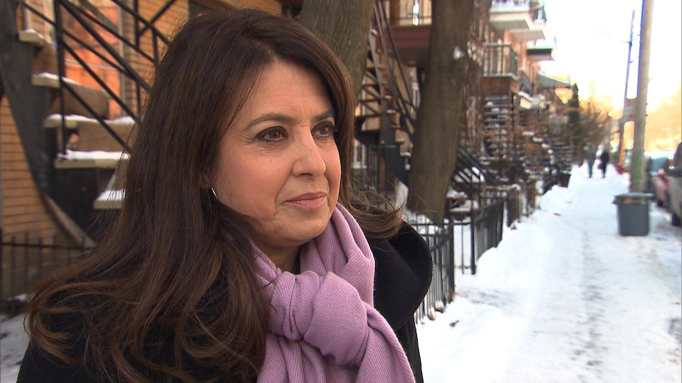 Une femme portant un manteau et un foulard regarde une journaliste lors d'une entrevue sur le trottoir enneigé d'une rue résidentielle.