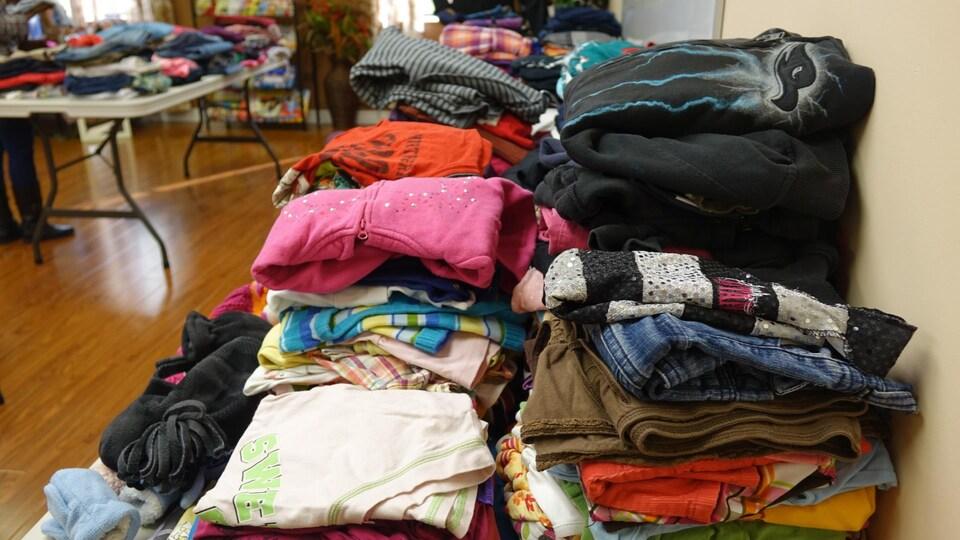 Des vêtements pliés sur des tables dans une salle.