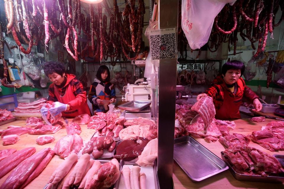 Des femmes préparent de la viande dans une boucherie de Pékin, en Chine.