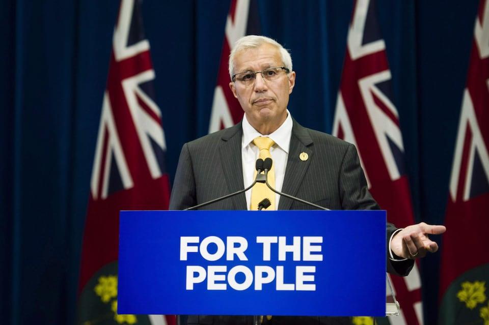 Une homme portant un complet et une cravate est debout derrière un lutrin sur lequel il est écrit en anglais: «Pour le peuple».