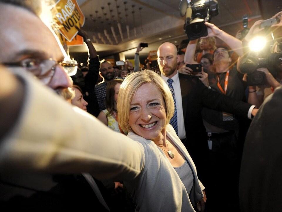 Une femme blonde est au centre de la photo. Elle tend sa main devant elle en saluant la foule qui l'entoure. Elle tente de ses frayer un passage entre ses partisans qui l'acclament et les journalistes qui la suivent.