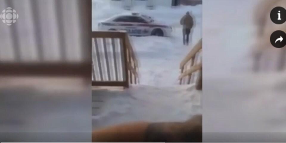 Un homme sur vidéo qui se dirige vers une voiture de police.