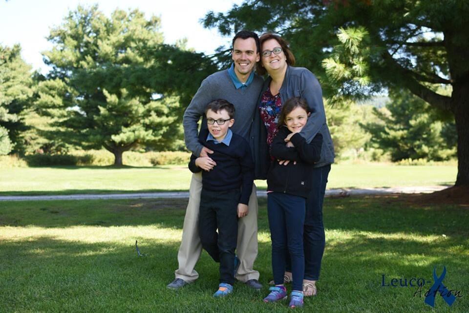 Un petit garçon, une jeune fille, un père et une mère prennent une photo sur un terrain de golf devant un arbre.