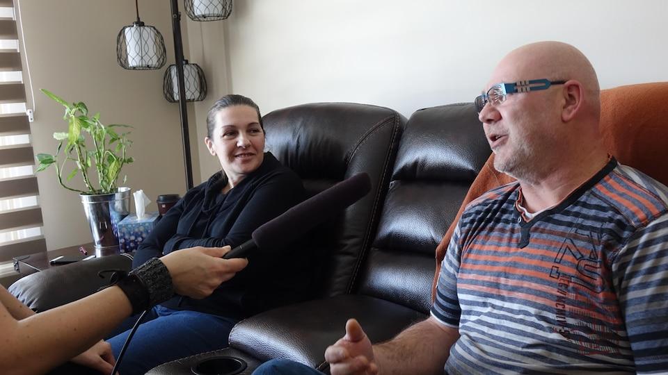 Un homme et une femme assis sur un sofa de cuir foncé parlent dans un micro.