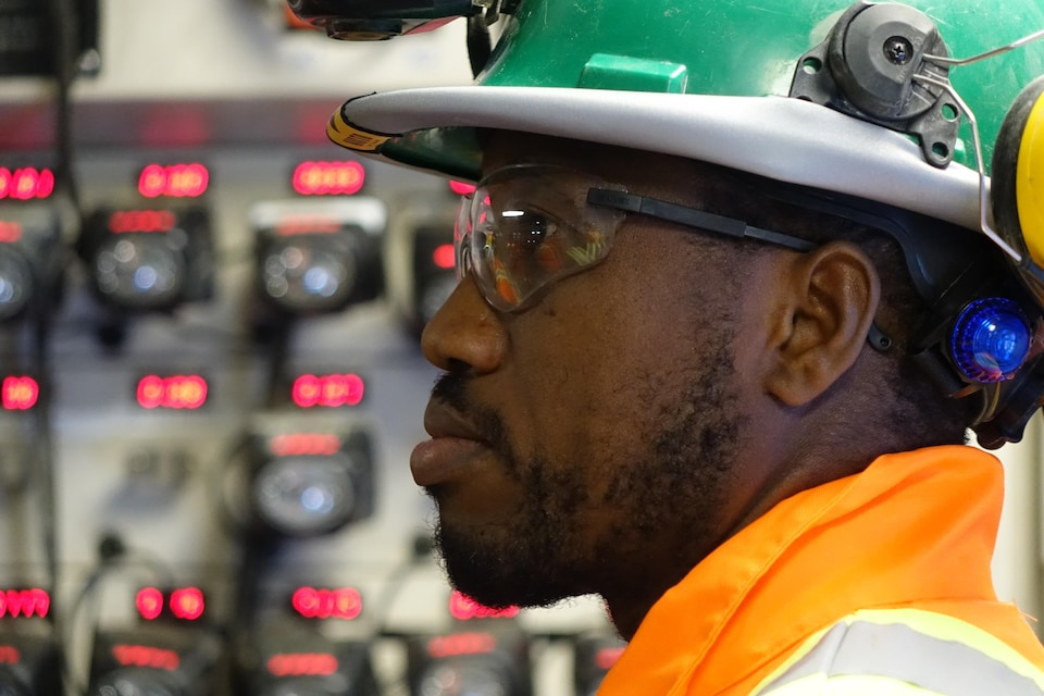 Vigan Conrad porte des vêtements de travail et un casque de sécurité.