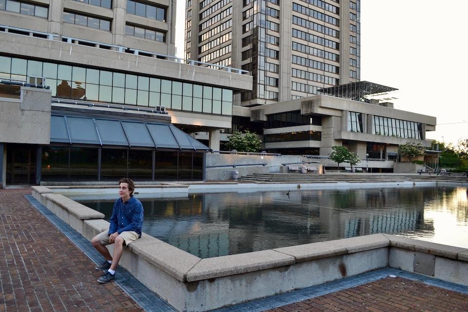 Un jeune homme assis au bord d'une fontaine située au milieu d'une place publique. Autour de lui, des édifices gouvernementaux en béton.