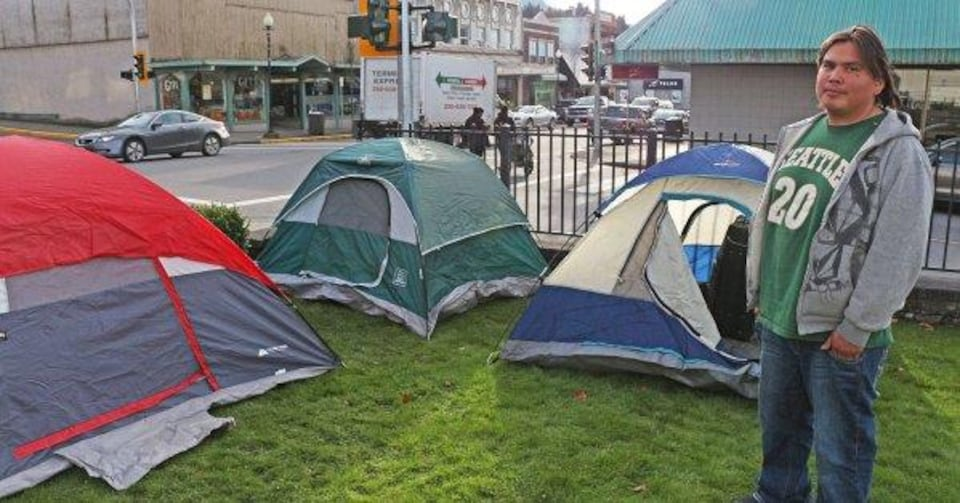 Un homme portant un jeans, un t-shirt et une veste à capuchon se laisse prendre en photo devant trois tentes montées sur la pelouse d'un terrain clôturé en bordure d'une intersection routière.
