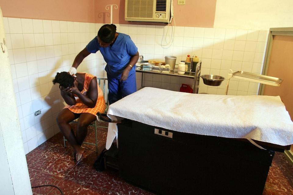 Une femme se tient la tête dans les mains tandis qu'une infirmière soigne sa blessure.