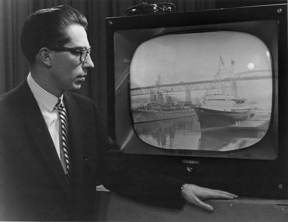 Dans un studio de télévision, l'annonceur Bruce Marsh fait la description de l'inauguration de la Voie maritime du Saint-Laurent, debout devant un moniteur de télévision dans lequel on voit le yacht royal Britannia faire son entrée dans la Voie maritime.