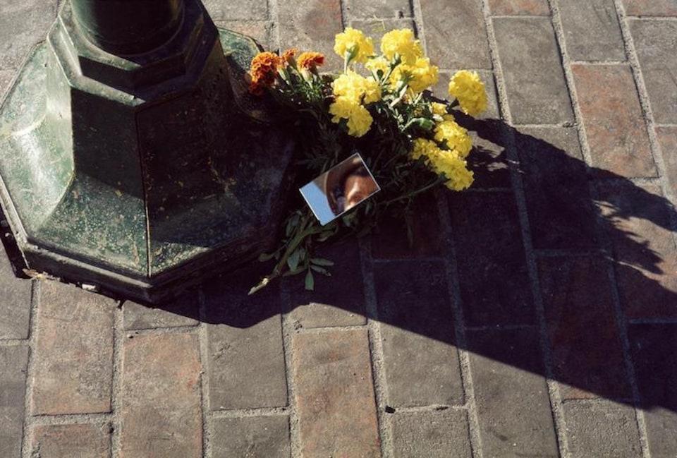 Au pied d'un lampadaire se trouvent un bouquet de fleur et un petit miroir dans lequel on voit la réflection de la photographe