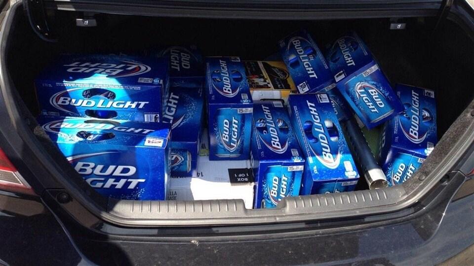 Le coffre d'une voiture rempli de caisses de bière