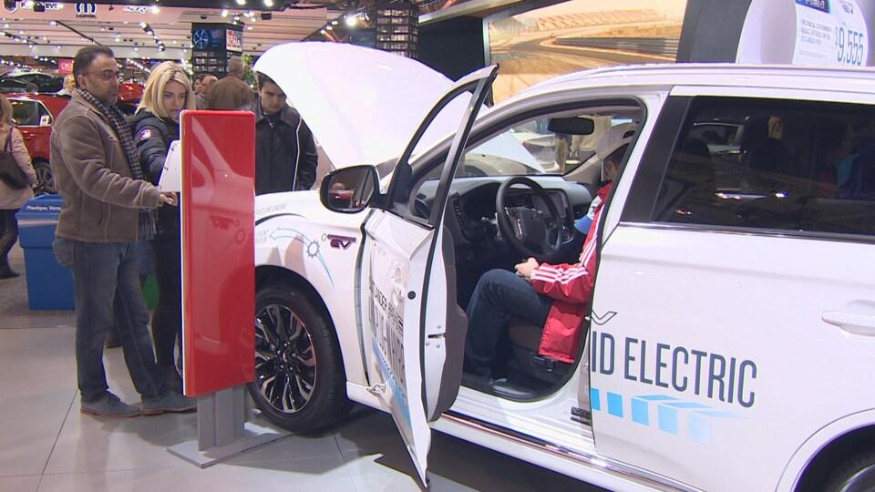 Des gens qui regardent une voiture électrique