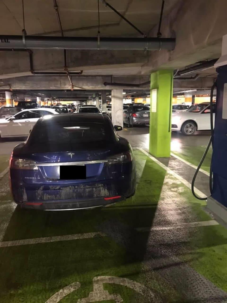 Un véhicule électrique bleu de marque Tesla occupe un espace de stationnement réservé peint en vert, mais il n'est pas branché à la borne de recharge à sa droite.