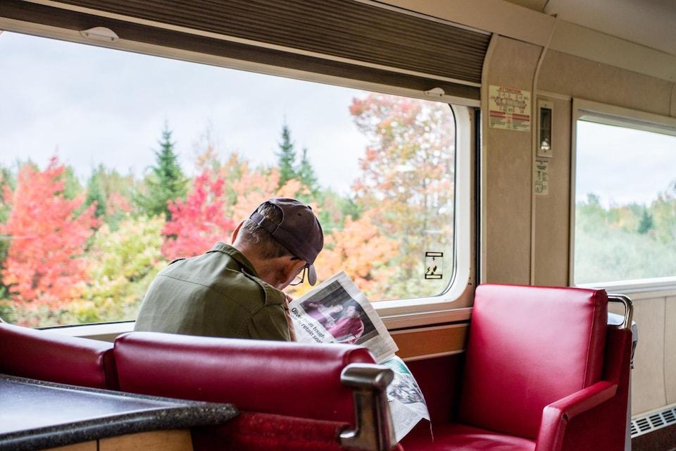 Un homme dans la voiture de la salle à manger du train.