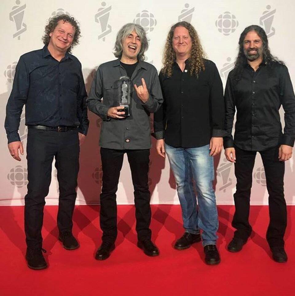 Quatre hommes sourient à la caméra avec leur prix dans les mains.