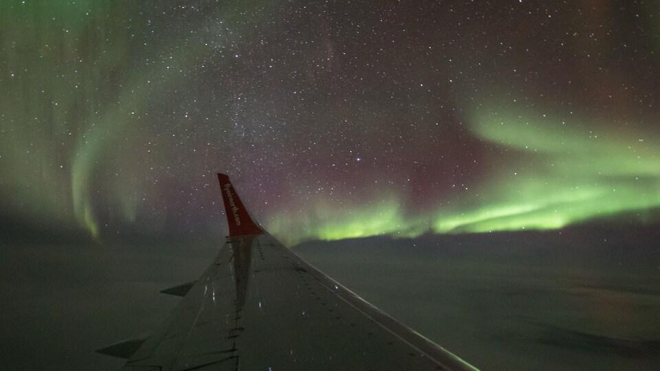 Des aurores boréales dans le ciel, vues par le hublot d'un avion