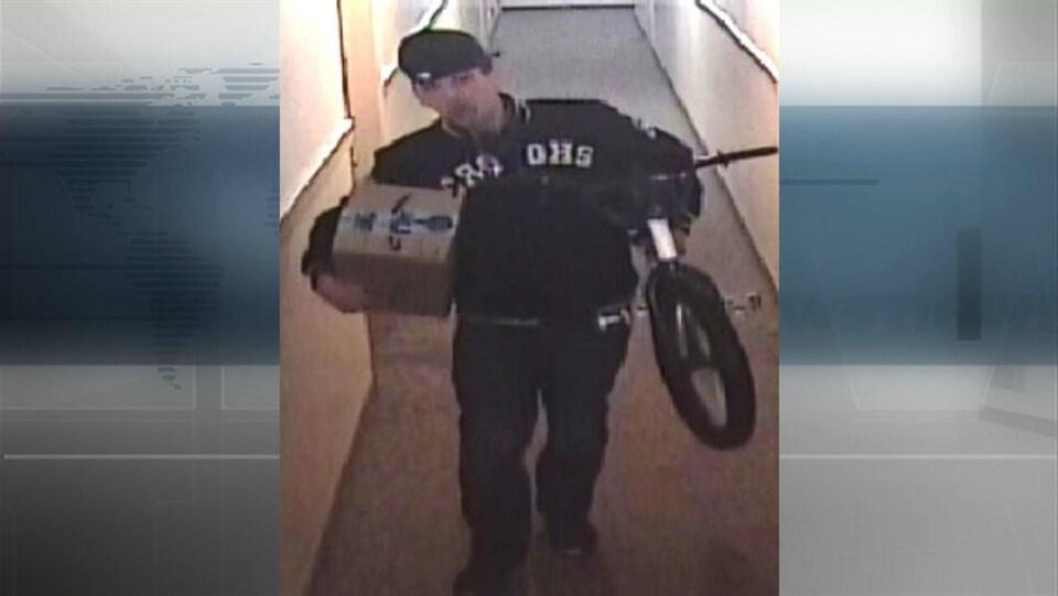 Une personne habillée en noir porte un paquet sous son bras droit et un vélo dans son autre main.