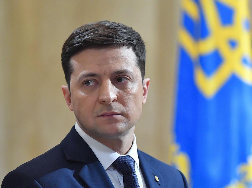 Un homme en complet devant un drapeau de l'Ukraine.
