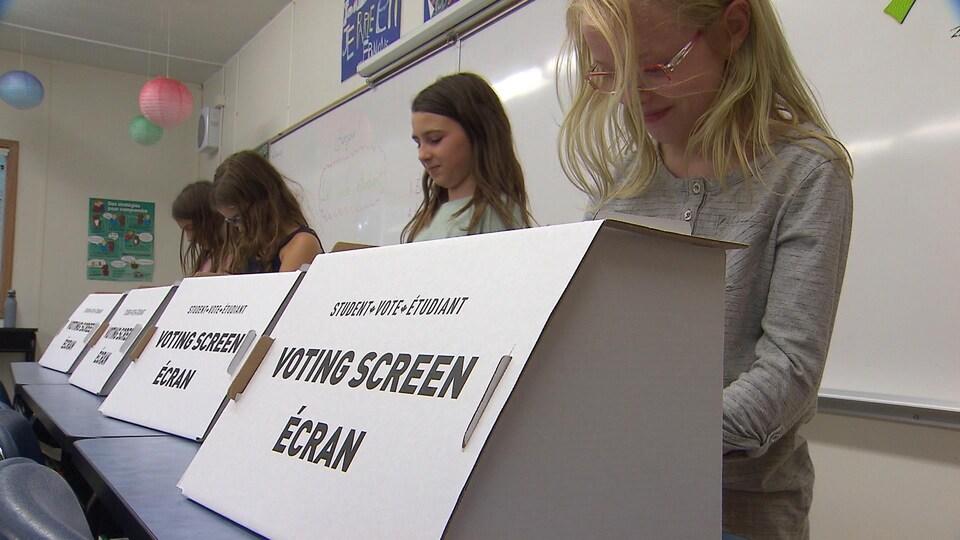Quatre élèves en train de voter dans un isoloir sur lequel est écrit «écran de vote étudiant».