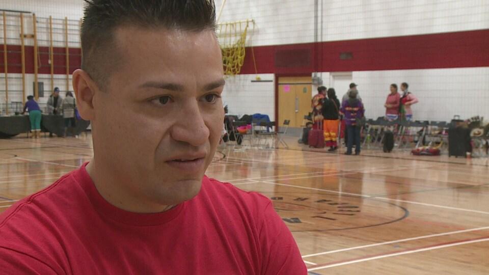 Un jeune homme autochtone vêtu d'un chandail rouge s'exprime à la caméra.