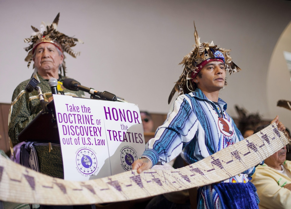 John Parsons, aka Tyhogeñhs, right, holds a historic wampum belt, that was commissioned by President George Washington ratifying the 1794 Treaty of Canandaigua, as Oren Lyons, left, Faitherkeeper, Turtle Clan, Onondaga Nation, answers question during a news conference in Washington, Tuesday, April 15, 2014. Onondaga Nation announced they will file a petition against the US with the Inter-American Commission on Human Rights (IACHR), claiming since 1788, 2.5 million acres of land have been stolen