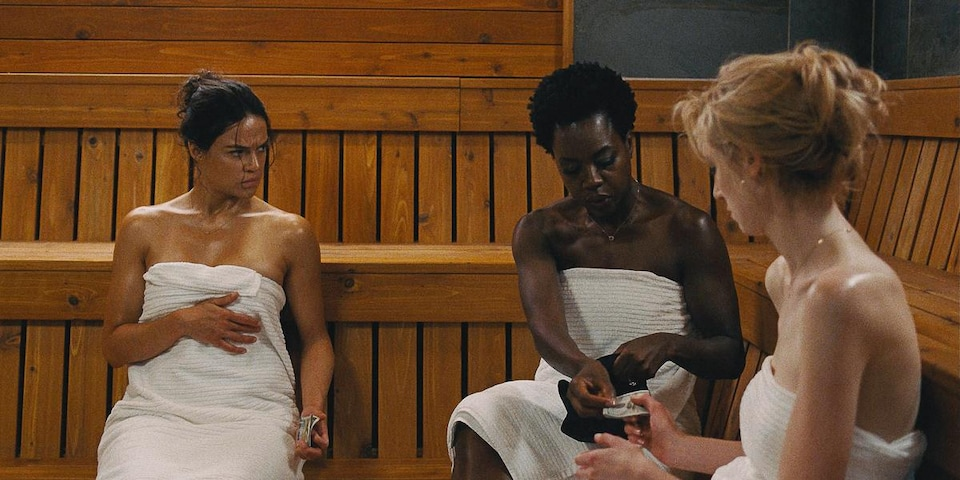 Les trois actrices dans un sauna portant une serviette blanche autour de la poitrine.