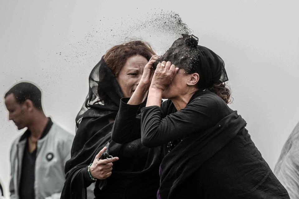 Une proche d'une victime de l'écrasement d'avion du vol ET302 d'Ethiopan Airlines se lance de la terre au visage alors qu'elle est en deuil sur le lieu de l'écrasement.