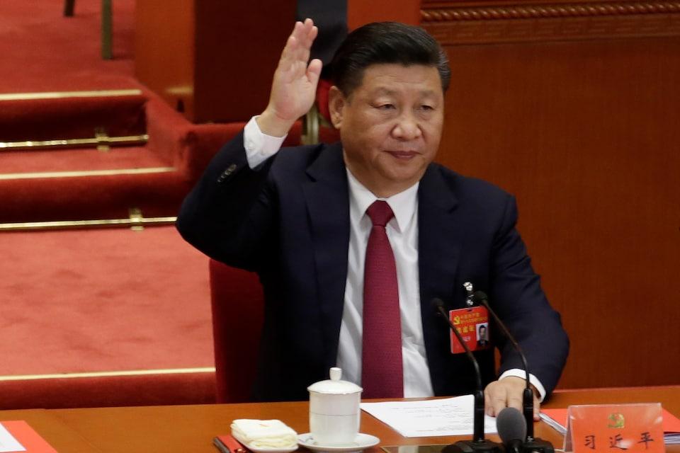 Xi Jinping lève la main.