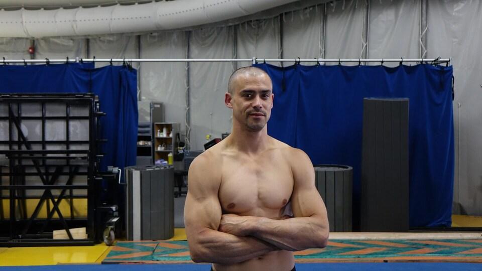 La photo montre Yann Arnaud, acrobate du Cirque du Soleil qui pose avec les bras croisés.
