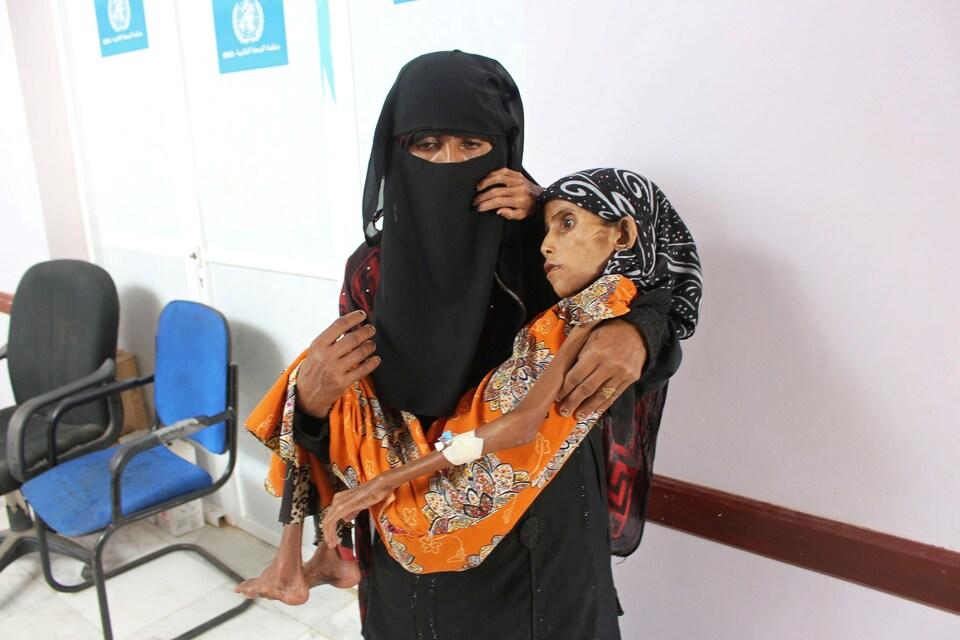 Une femme en burqa tient une femme extrêmement maigre dans ses bras.