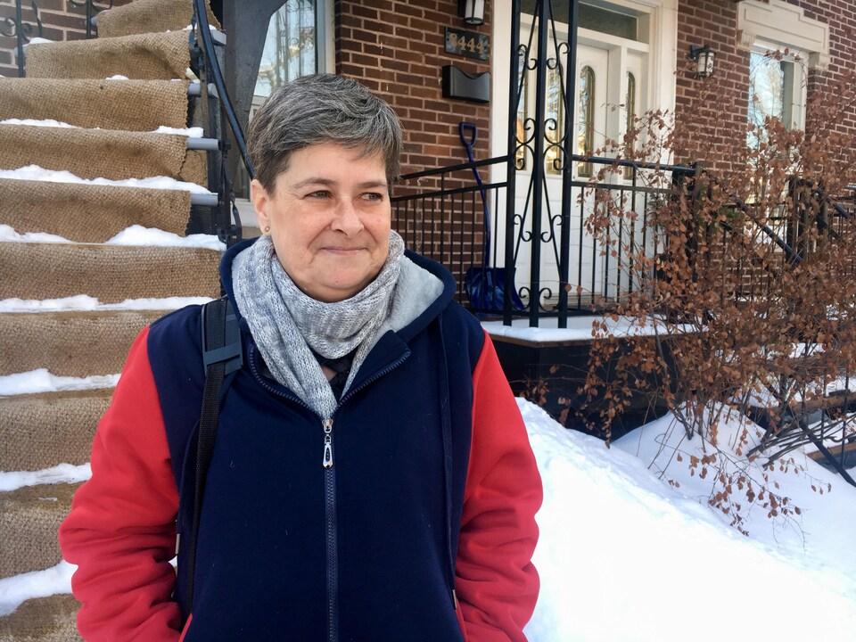 Yolaine Lafleur, debout, devant l'immeuble où habite aujourd'hui sa fille, dans le quartier Villeray, à Montréal.