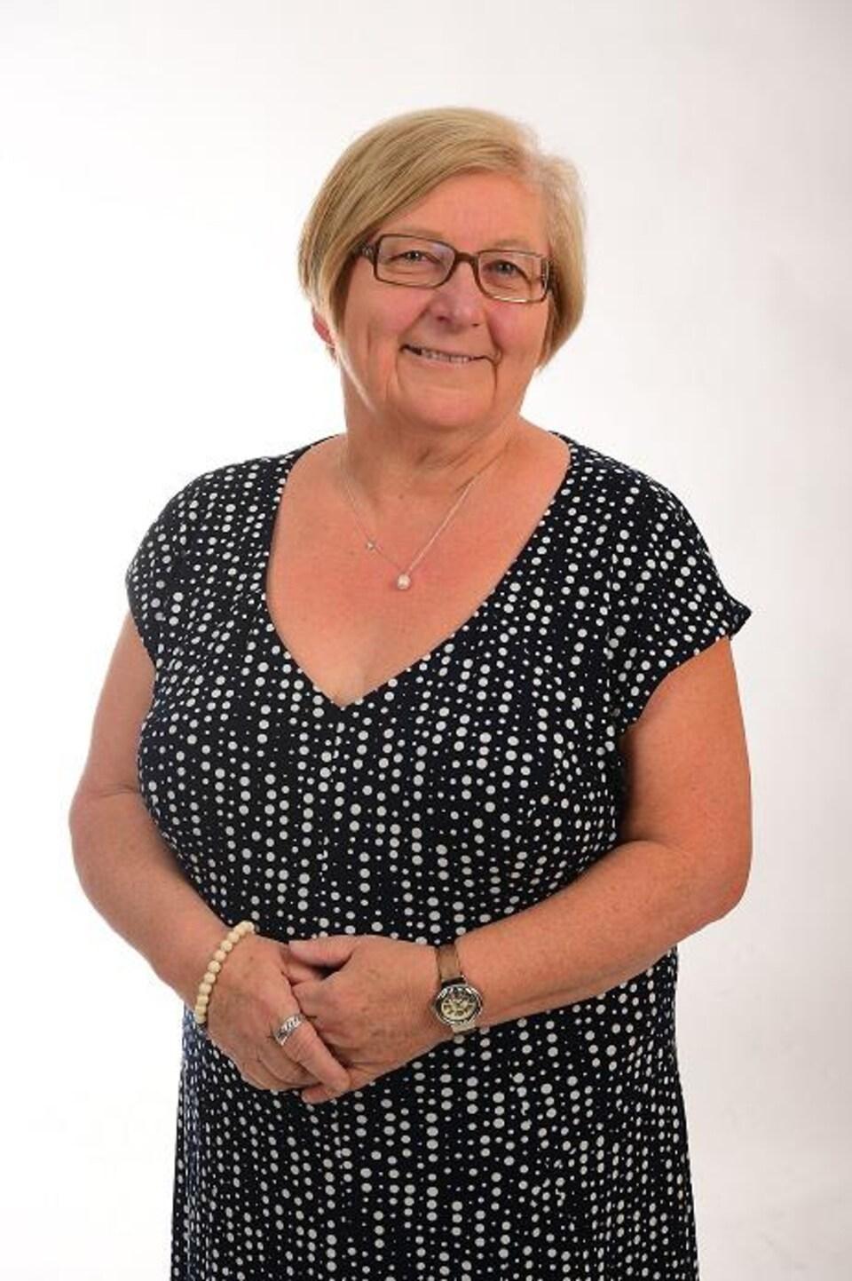 Une femme souriante, Yolande Dupuis, pose pour un photographe.