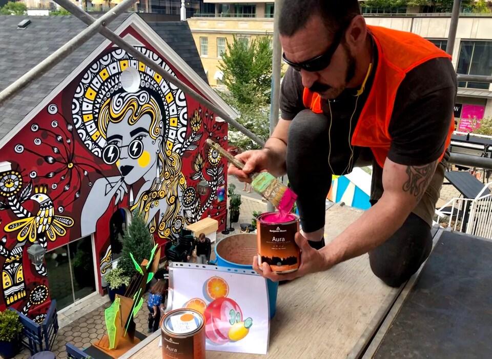 Un homme trempe son pinceau dans un pot de peinture.