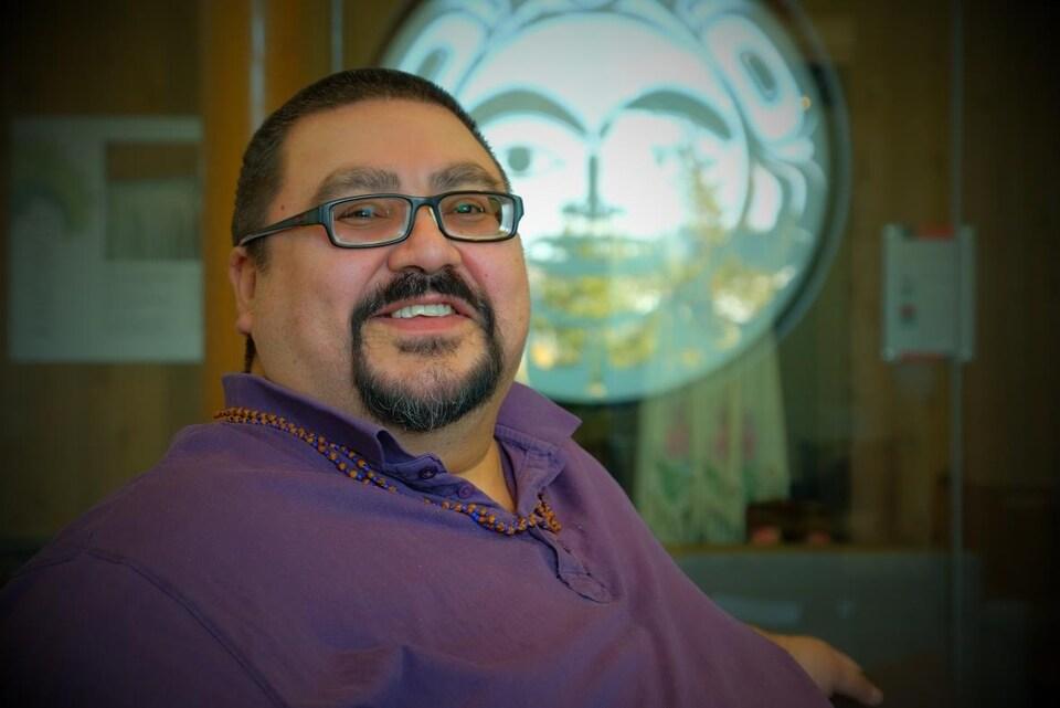 Un homme sourit devant une oeuvre autochtone sur un mur.