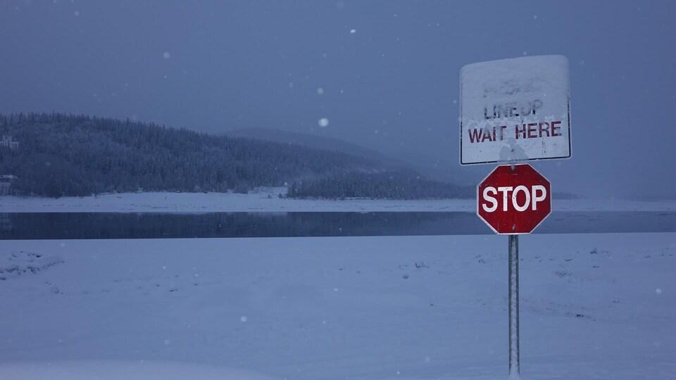 Un panneau d'arrêt à l'endroit où un pont de glace l'hiver et un traversier l'été relient les deux rives.