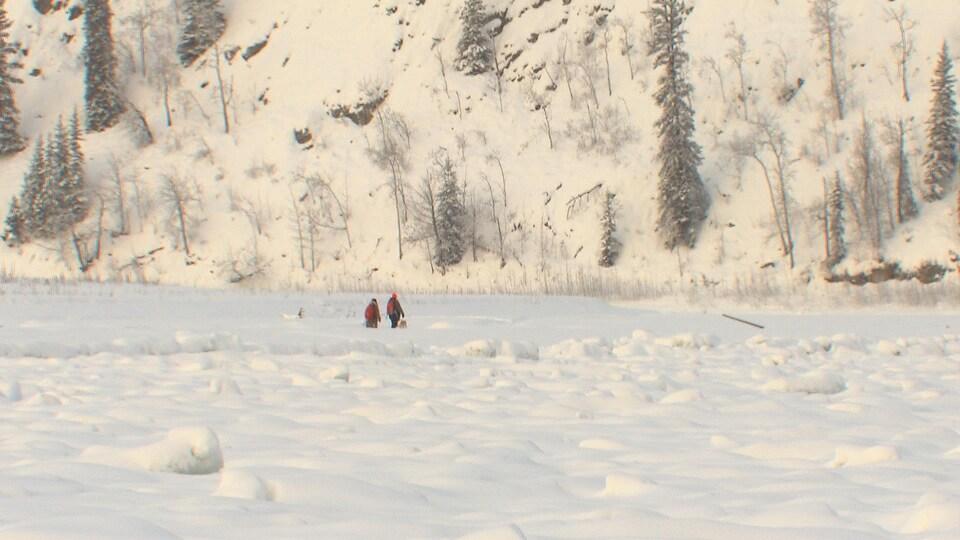 Deux personnes traversent le fleuve à pied.