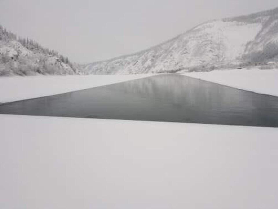 Vue d'une étendue d'eau ouverte à partir d'un pan de glace entre deux rives