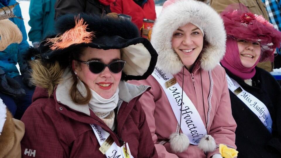 Trois femmes sont assises. Elles portent des chapeaux à plumes et des bandeaux de miss.