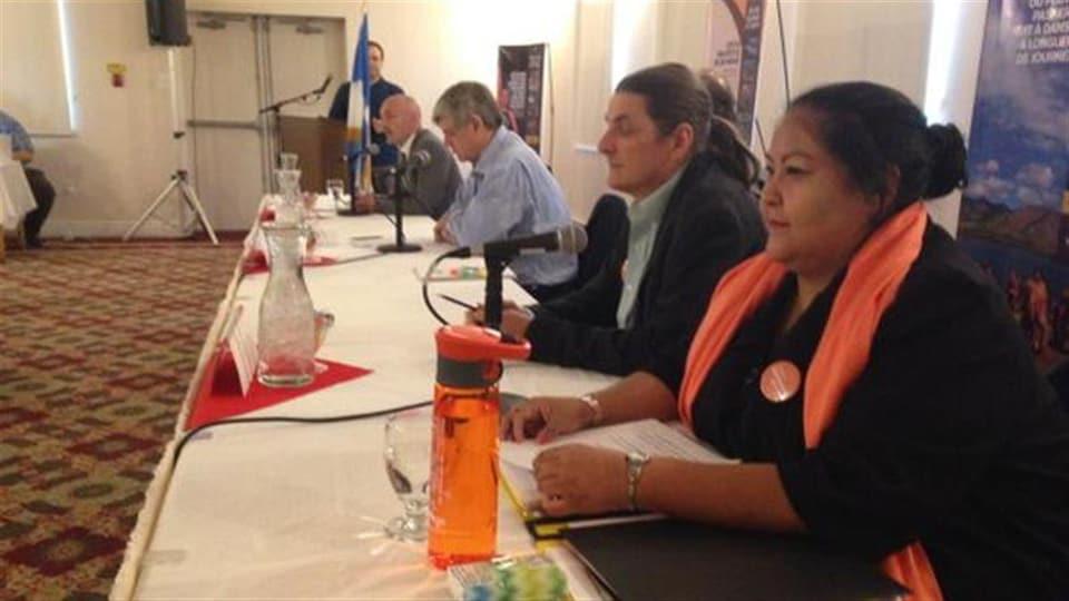 Une femme est assise à une table, un micro devant elle. D'autres personnes sont assises à la même table à côté. Il y a une gourde et un verre d'eau sur la table en premier plan.