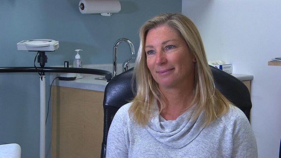 Une femme dans un cabinet médical sourit.