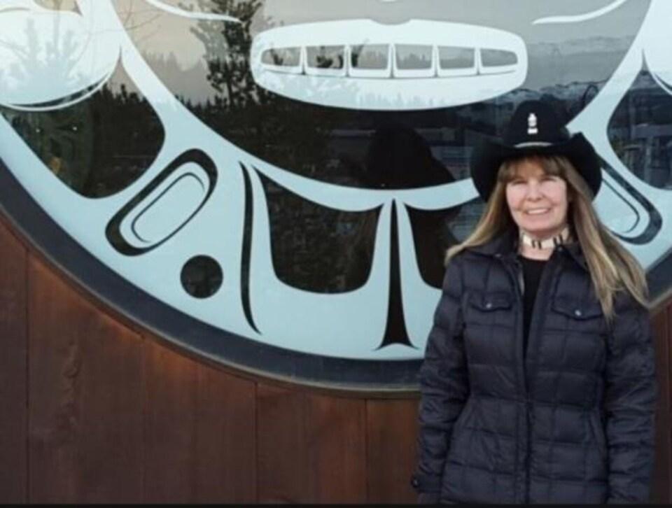 Une femme portant un manteau d'hiver et un chapeau de cow-boy.