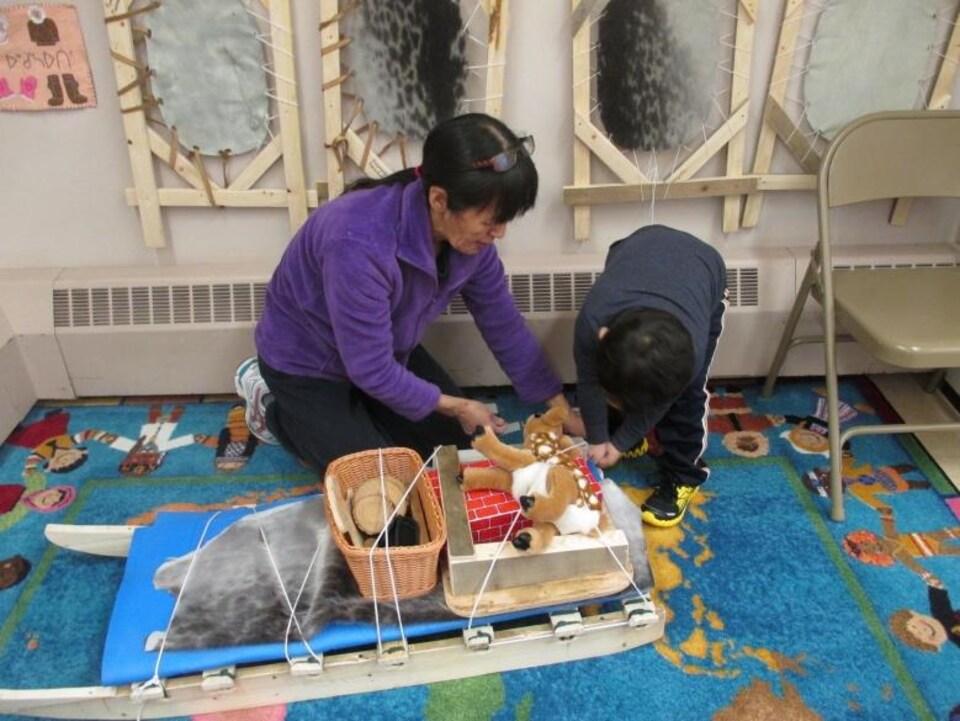 Une femme est accroupie sur un tapis. Elle aide un jeune garçon à attacher des jouets sur un traîneau.