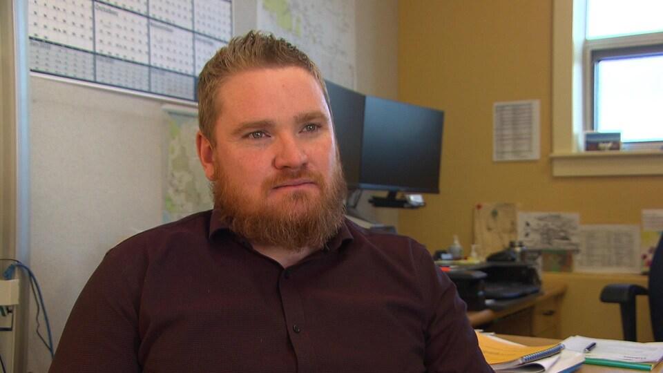 Un homme dans un bureau avec des ordinateurs derrière.