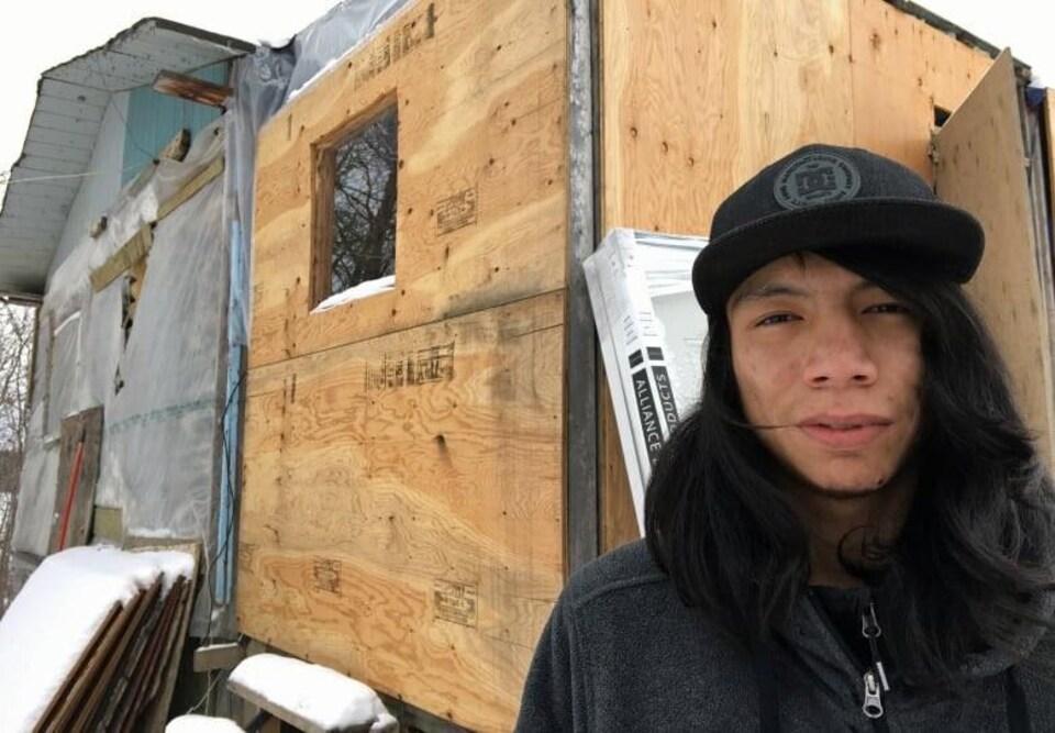 Un jeune homme devant une maison en contreplaqué.