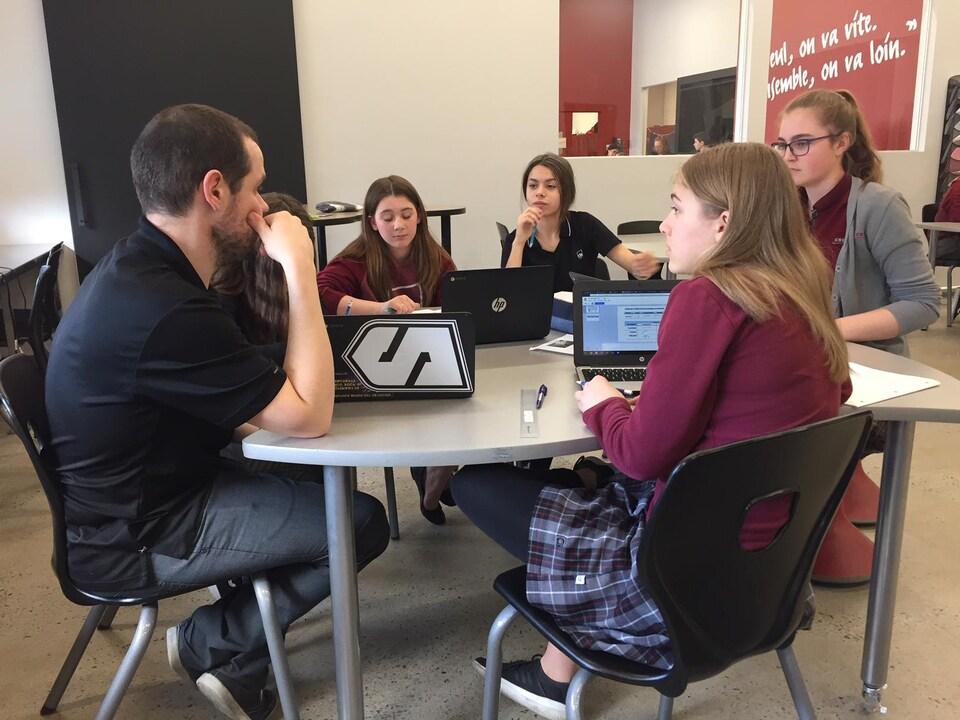 Des élèves discutent en petit groupe avec l'un de leurs enseignants.