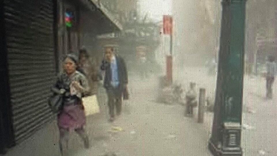 Des piétons marchent dans un nuage de poussière.