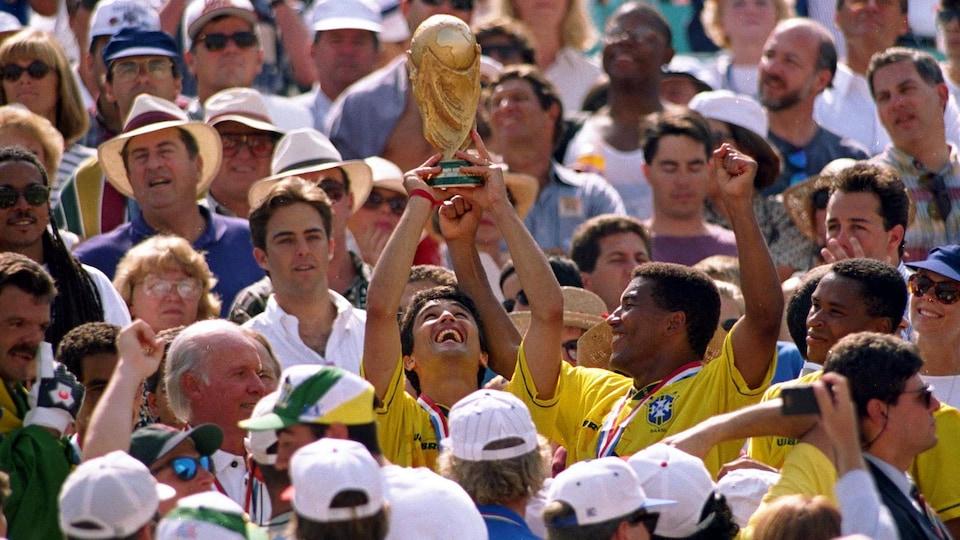 Il soulève la précieuse coupe du monde au milieu d'un groupe de partisans.