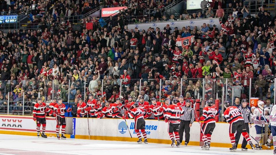 Des milliers de spectateurs célèbrent un but pendant que les joueurs se félicitent lors d'un match l'an dernier.