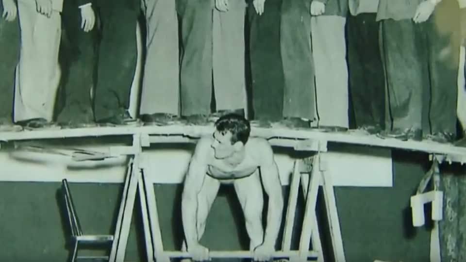 Une homme soulève avec son dos des gens installés sur une planche